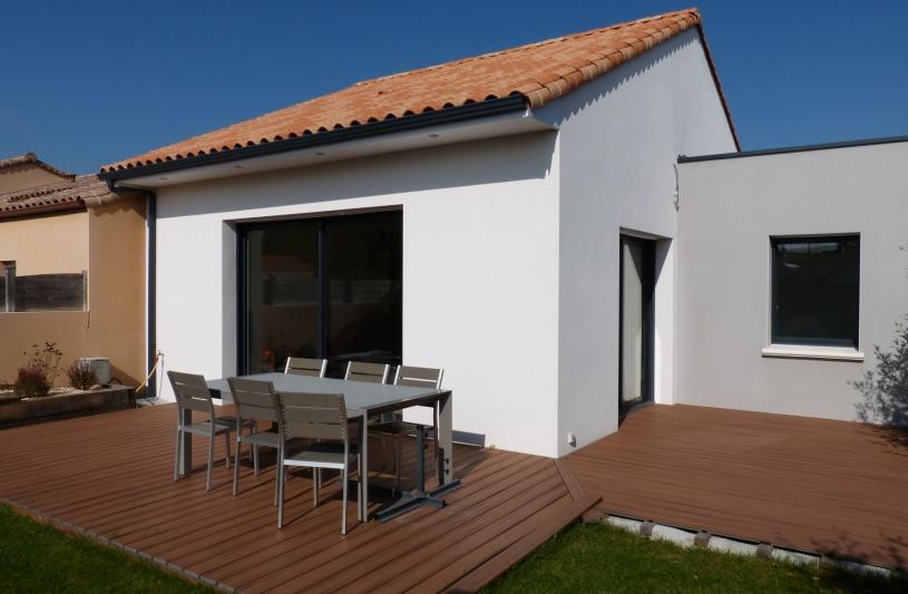 Une partie de la toiture traitée en toiture terrasse afin de respecter les règles d'urbanisme lui confère une esthétique plus moderne. En outre la porte d'entrée placée dans  l'angle sous un pan de toiture coupé contribue à l'articulation entre les 2 volumes.