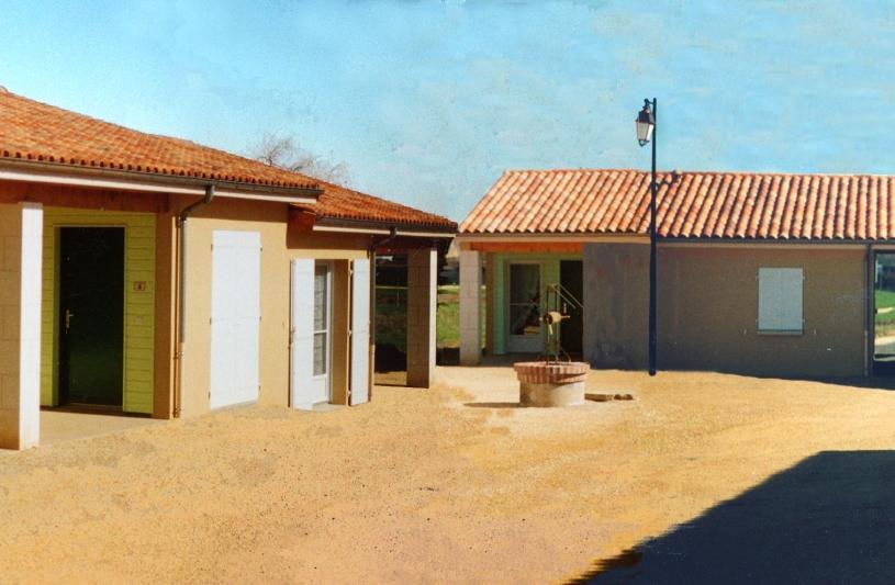 Les logements sont organisés autour de l'ancienne cour de ferme; Derriére le porche, la salle des fêtes.