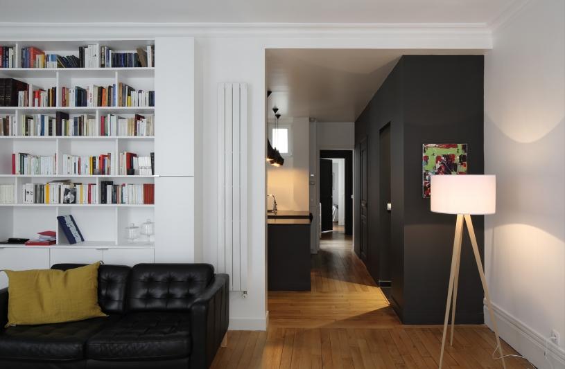 Liaison entre le salon et l'entrée, bibliothèque, rangements ouvert et fermé, radiateur, contraste blanc et noire, parquet, mur d'accent, éclairage, couloir.