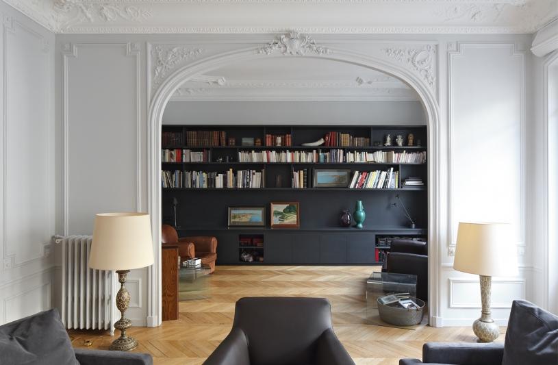 Grand double salon Haussmannien, contraste ancien et contemporain, moulures, parquet en pointe de hongrie,bibliothèque noire, rangements ouverts et fermés, banc, salon confort, étagères murales.