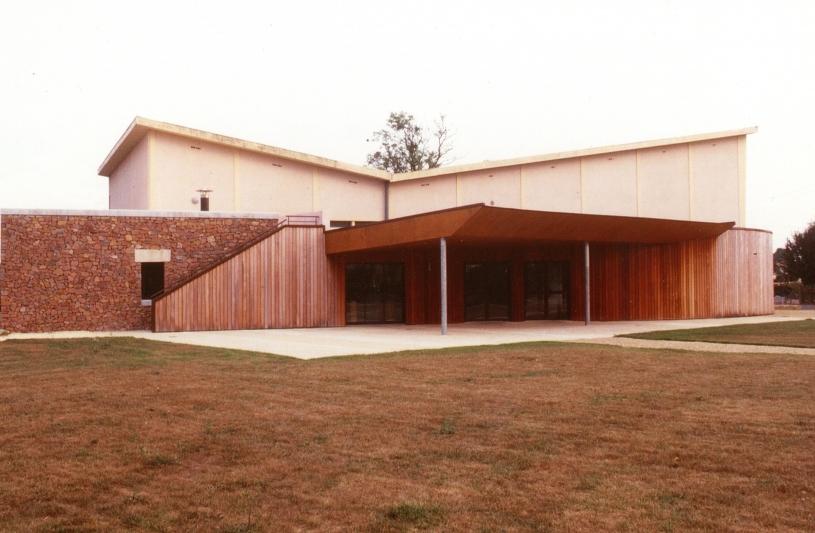 C'est une extension d'une salle des fêtes de village, en ossature bois et clin d'IPE, par un hall d'accueil, cuisine, sanitaires;
