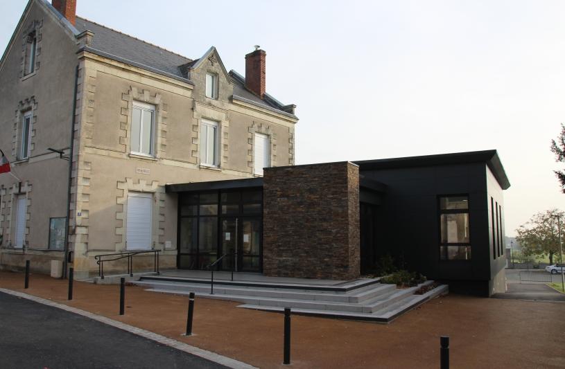 L'entrée est traitée toute en transparence avec débordement de toiture formant auvent. Un mur habillé en pierres de schiste renforce le signal de l'entrée et fait écho à la pierre locale.