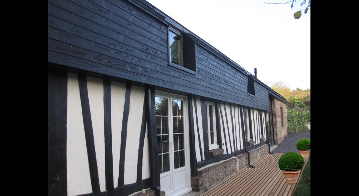 Une ossature bois revêtue d'un bardage bois de teinte noire a été utilisée pour modifier la toiture existante et permettre l'aménagement des combles de la longère.
