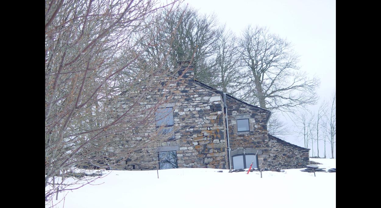 Bâtiment totalement reconstruit en pierres, toiture lauzes.