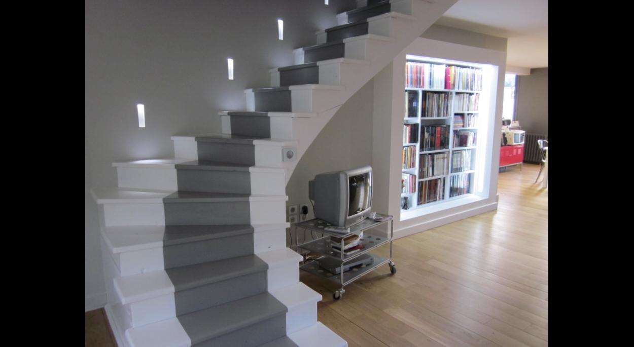 Escalier d'accès à l'étage et coin bibliothèque.