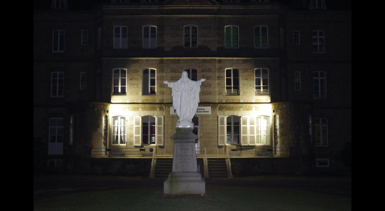La façade du bâtiment château est mise en valeur par une lumière en pied