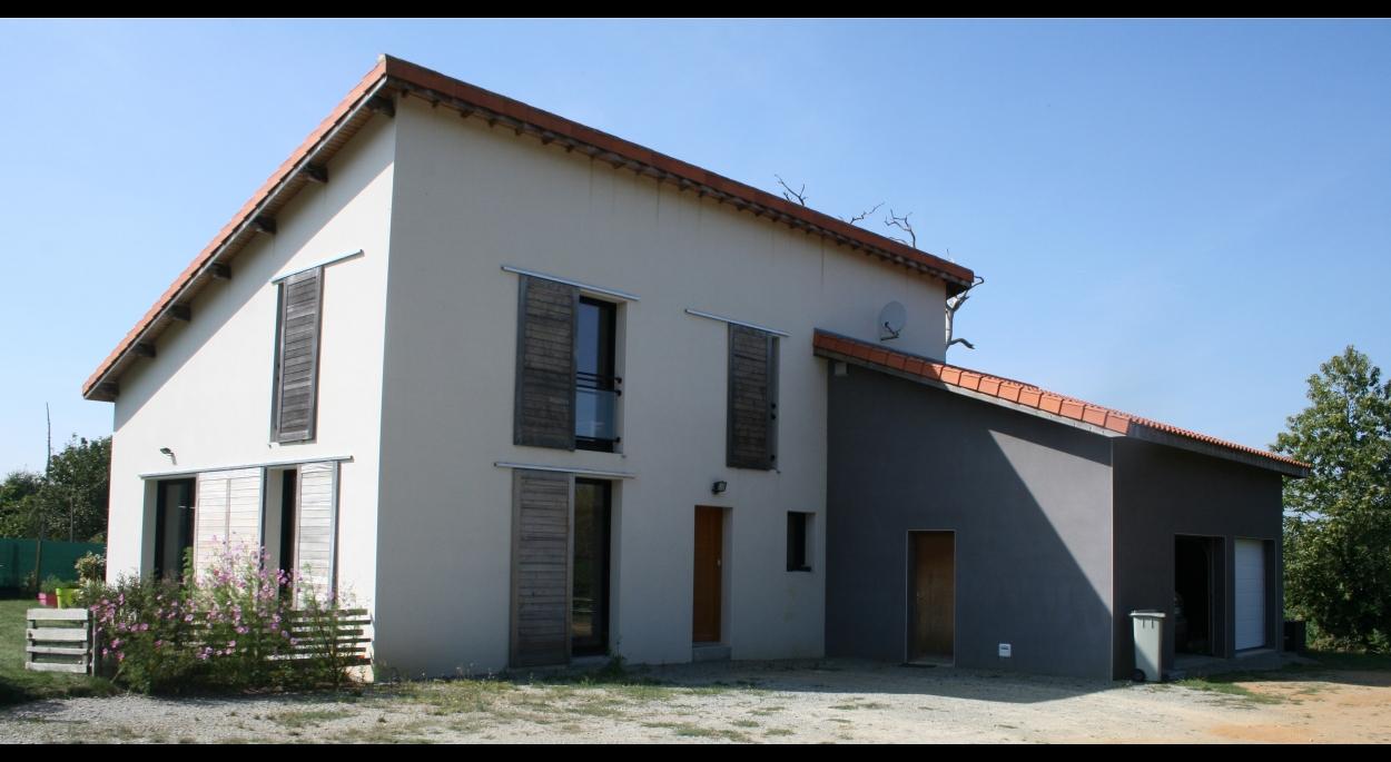 Maison avec toiture tuiles mono-pente, enduit ton blanc et ton gris, volets coulissants bois, gabions,