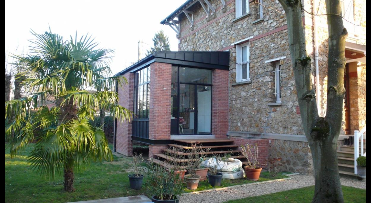 vue de l'extension et de la terrasse bois avec l'escalier permettant l'accès au jardin