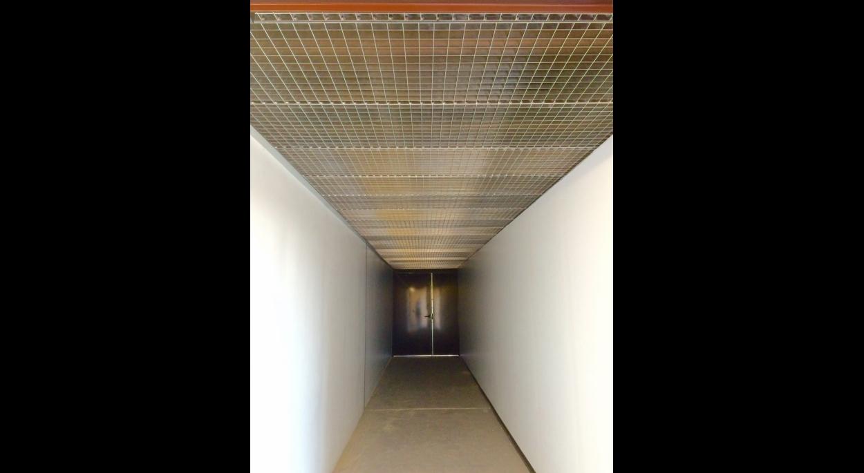 Les grilles en caillebotis, en guise de faux-plafond, laissent une ouverture sur toute l'hauteur du local