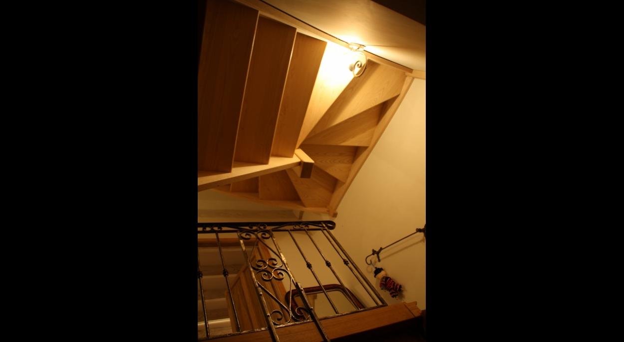 Réalisation d'un escalier en bois de frêne olivier . Garde corps en fer forgé de récupération retouché par un artiste.