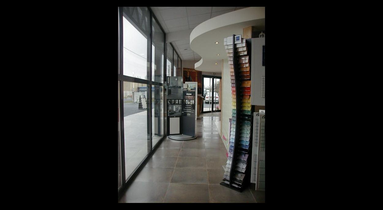 Intérieur du bâtiment avec vue sur un ilôt de présentation des carrelages avec faux-plafonds cintrés.