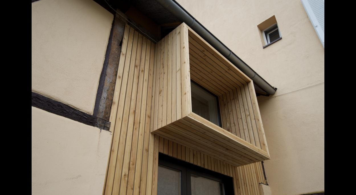 La porte cochère remplacée par un mur en ossature bois isolé en fibres de bois avec un bardage de mélèze ajouré.