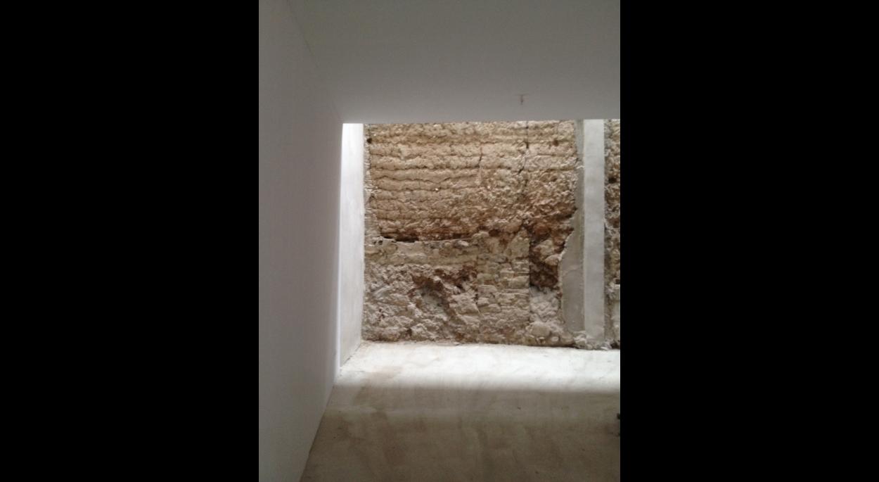 Deux pans d'un mur en terre, datant de la création de la bastide est conservé visible. Une verrière supportée par des piliers protège et éclaire ce mur.