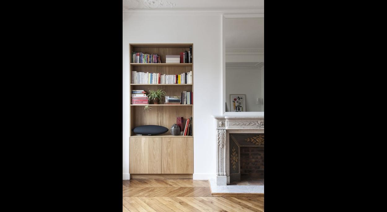 profitant de l'embrasure d'une ancienne porte, les architectes ont dessiné une étagère en chêne.