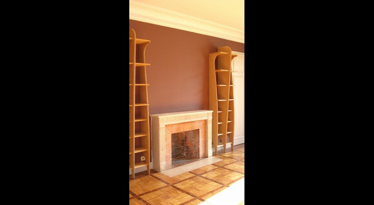 Deux colonnes encadrent la cheminée. Ensemble de bibliothéque murales en bois blond. ARCHI-V.O