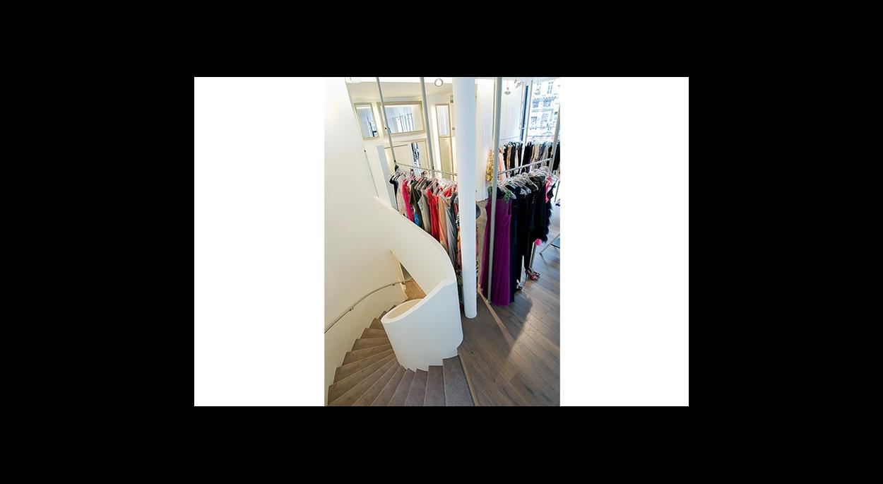 salle avec produit sur portant, ouverture sur rue, vitrine, parquet au sol, escalier tournant, blanc, poteaux structure
