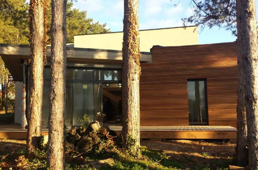 Une fenêtre ouverte sur un sous-bois: de la conception jusqu'à la réalisation avec l'idée permanente d'intégration au site avec préservation des arbres existants. Système constructif : toiture terrasse végétalisée, béton cellulaire et  bardage bois en red cedar, terrasse extérieure bois en IPE.