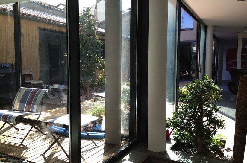 Les baies coulissantes qui entourent le patio, permettront, par beau temps, d'ouvrir entièrement la maison vers le patio et de gommer ainsi les limites entre le dehors et le dedans.