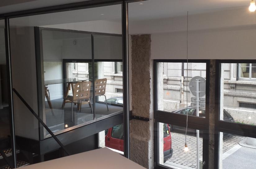 Pour l'agence de design en communication : Exploitation de la hauteur de la hauteur du local avec ses 2 niveaux - Ensemble structure en métal brut et vitrages pour un apport de lumière nautrelle au maximum ,