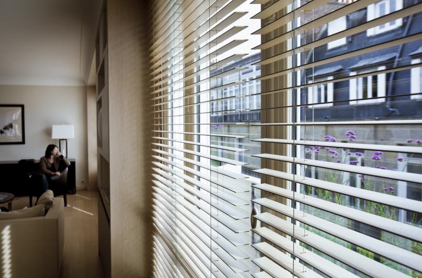 Fenètre ouverture sur extérieur, store, perspective sur salon, canapé, lumière, parquet au sol, bois, contemporain