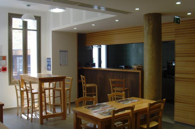 La salle du bistrot avec en arrière plan, le bar et la cuisine ouverte.