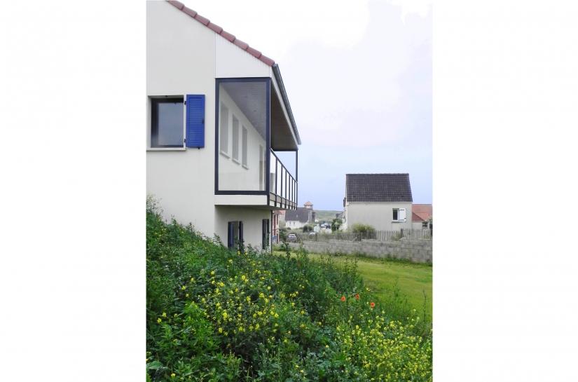 un balcon avec vue sur la mer vient prolonger le salon de l'étage et protéger la façade des embruns
