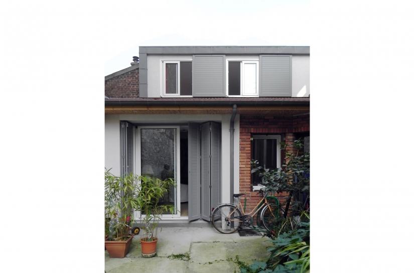 vue depuis la cour, façade avec volets coulissants avec rail intégré à la toiture
