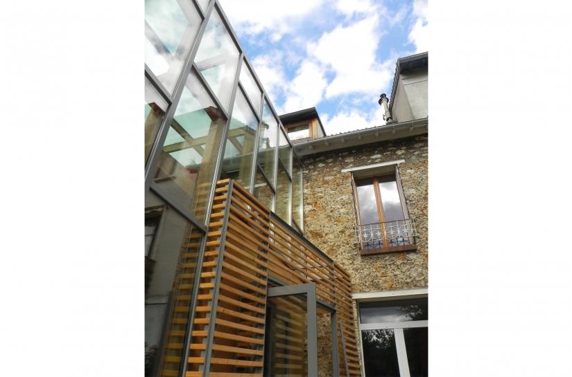 un contraste fort de matériaux (verre de l'extension et pierre de la maison existante) mis en relation par les reflets des vitrages
