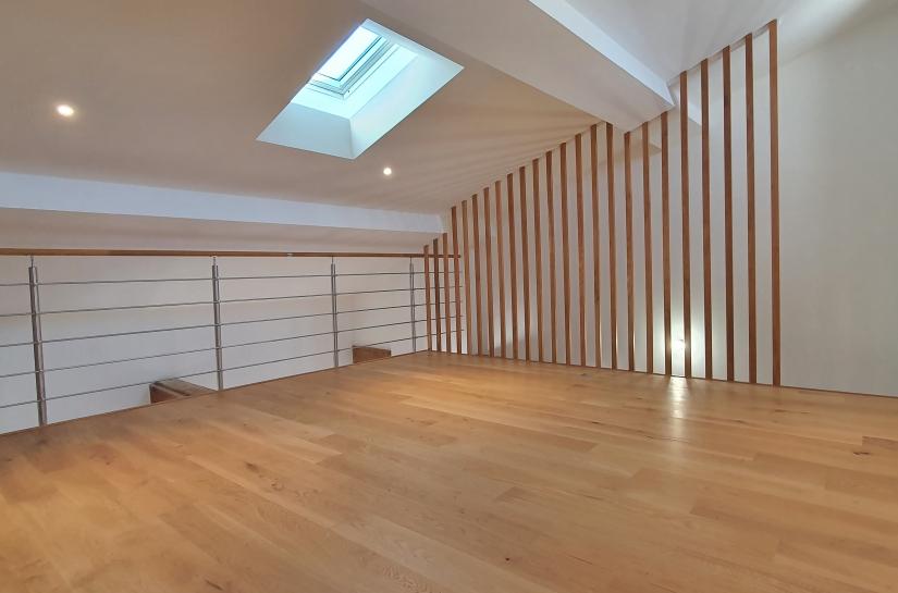 La mezzanine dans les combles, qui apporte également de la lumière au niveau bas