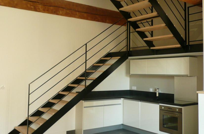 Un escalier conçu en 2 volées, accueillant la cuisine sous son palier